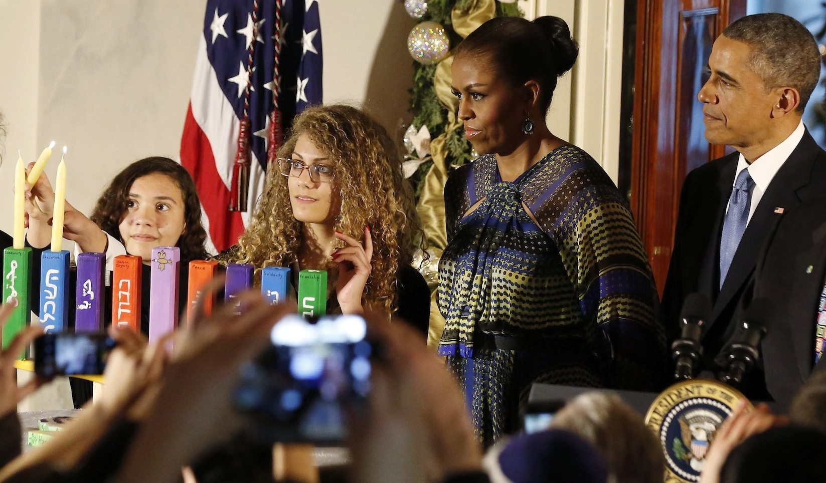 U.S. President Barack Obama is joined by Rebecca Bardach, Inbar Shaked Vardi, Mouran Ibrahim and first lady Michelle Obama as they attend a Hanukkah reception in the Grand Foyer of the White House in Washington