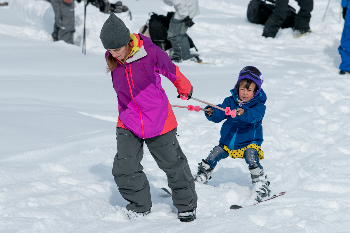 Nayla tows a 5-year-old girl up the ski hill.
